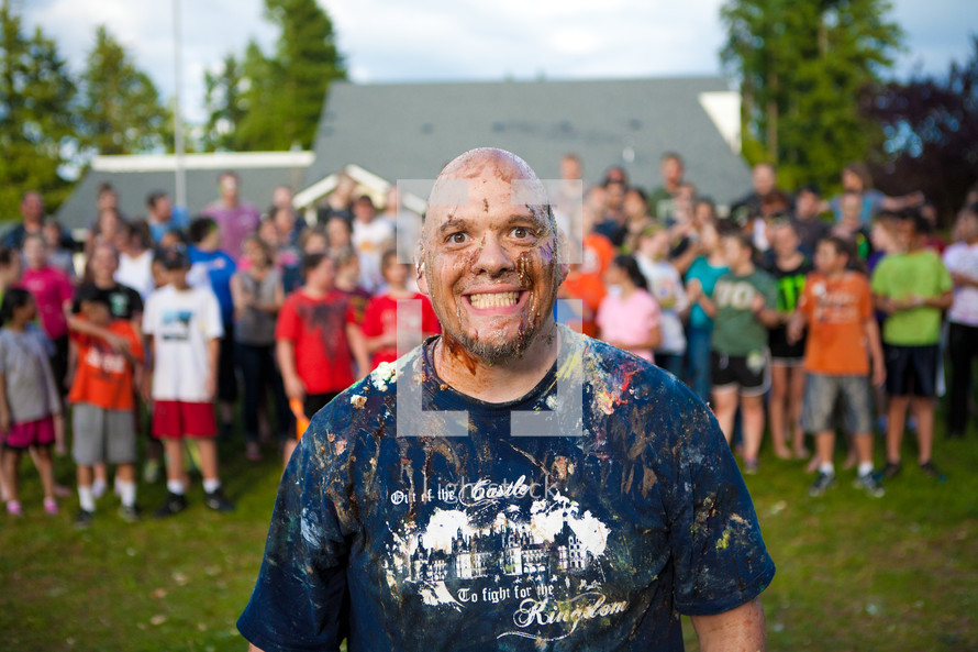 A youth pastor smiling wildly, covered in colorful cake and frosting, in front of a rowdy youth group in the background.