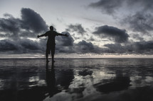 a man standing on a beach on wet sand with opened arms  at sunset