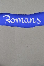 Romans - torn open kraft paper over intense blue paper with the name of the letter from Paul to the  Romans