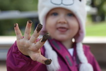 toddler girl playing in mud