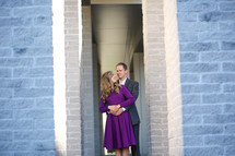 A couple stand together in a doorway.