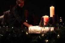 A man lighting Christmas candles.
