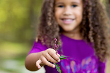 a young girl holding a small purple flower