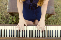 woman playing the piano outdoors