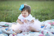 Smiling toddler girl in a tutu sitting on a quit in a field of grass.