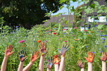 finger paint on the hands of kids standing outdoors in a field of flowers