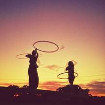 Couple hula hooping at sunset