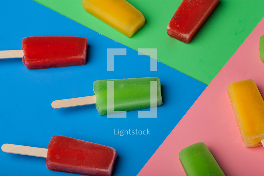 Brightly colored popsicles arranged on different colored papers.