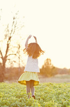girl child running in a field with her hands in the air