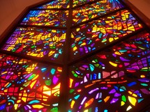 A large and colorful stained glass window lighting up a church giving the light and warmth needed to worship and feel the glow of Heaven pouring in to light up the room.
