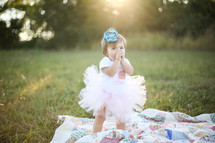Toddler girl in a tutu standing on a quit in a field of grass outside.