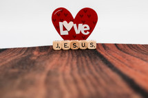 paper heart with the word love and scrabble pieces with the word Jesus