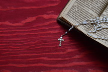 rosary beads on the pages of a Bible