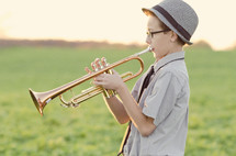 Boy in a hat playing trumpet in a grassy meadow.