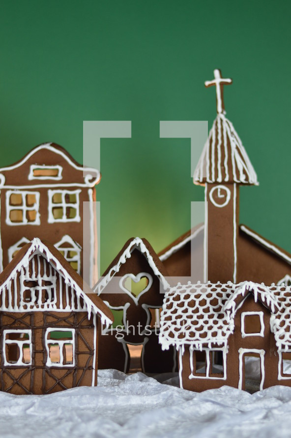 home made gingerbread village in front of green background on white snowlike velvet as advent decoration