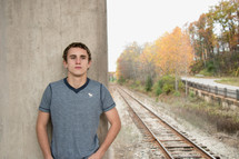 man standing near railroad tracks