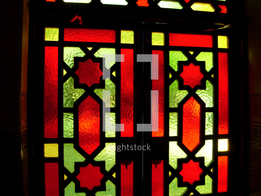 A set of beautiful red, gold stained glass windows adorning a church sanctuary, church office or pastor's study that can be opened to let light in the church and adorn the room with color.
