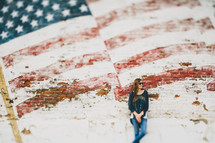 A woman leaning against a wall with a faded flag painted on it.