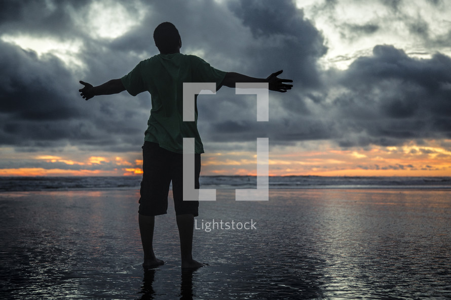 a man standing on a beach on wet sand with open arms at sunset