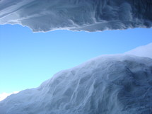 View out of a glacier cave into the bright sky,