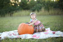 toddler girl on a blanket in the grass with a pumpkin