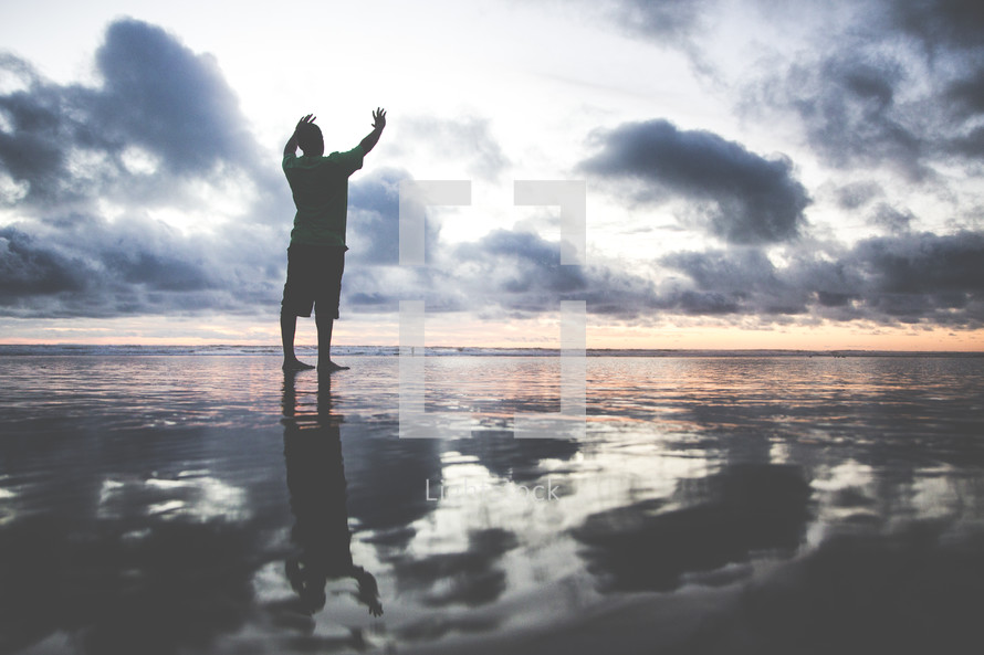 a man standing on a wet beach with raised hands at sunset
