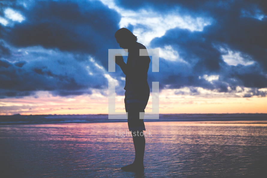 a man standing on a beach on wet sand with praying hands at sunset
