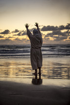 Jesus with raised hands on a shore at sunset