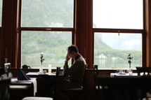 man sitting along at a table at a restaurant