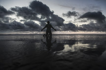 a man kneeling on a beach on wet sand at sunset