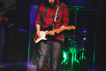 a man playing an electric guitar on stage