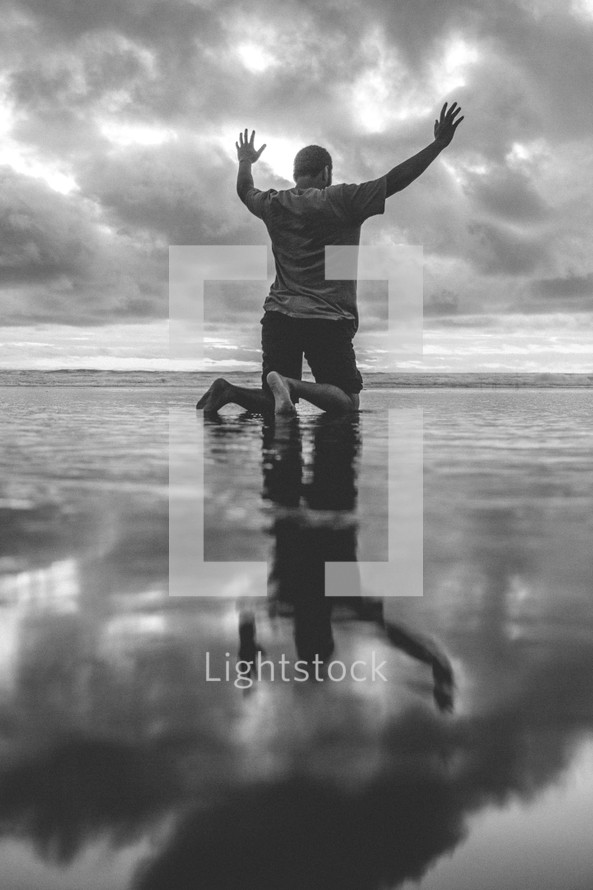 a man kneeling on a beach on wet sand with hands raised at sunset