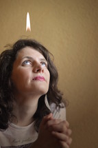 a woman praying with a flame above her head