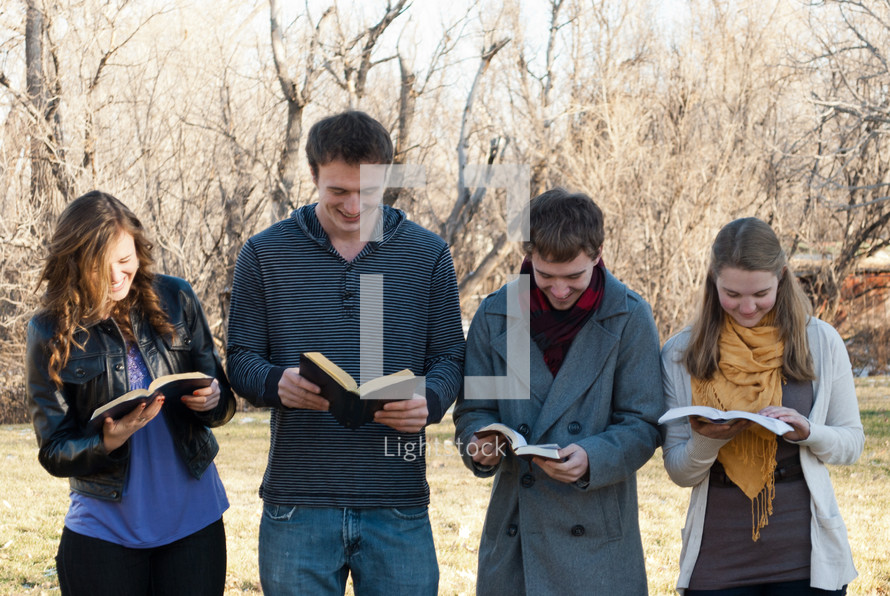 college students reading their Bibles outdoors during a Bible study