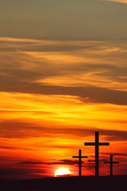 Sunrise behind three crosses in silhouette