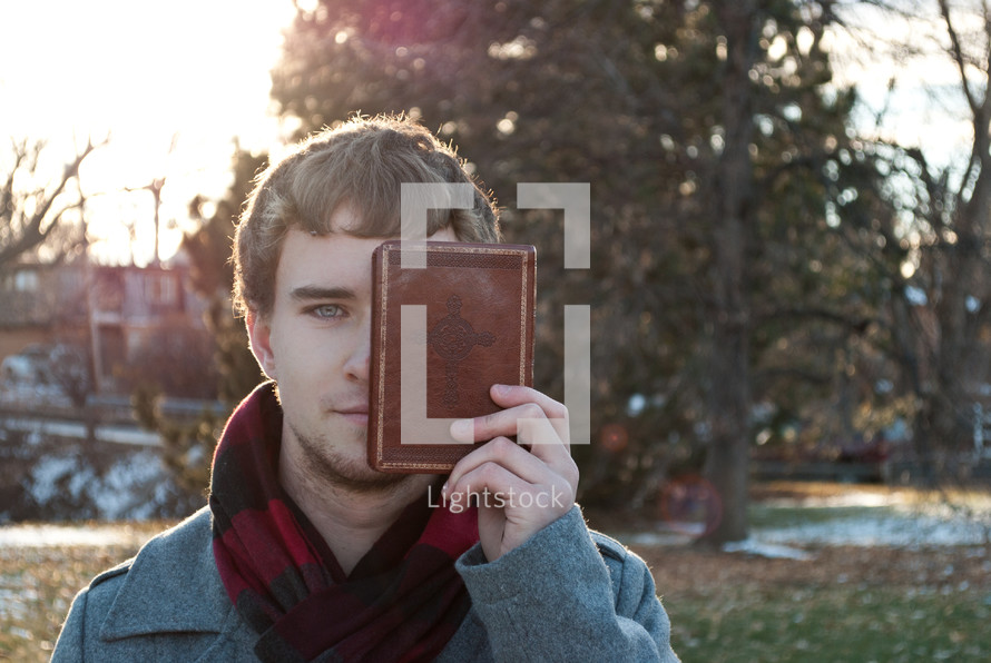 college student holding a Bible in front of half his face