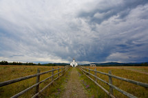 Pathway to a small country church under stormy sky