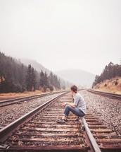 Girl sitting on railroad tracks