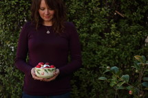 a woman holding a bowl of Christmas ornaments