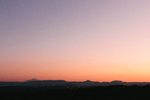 The sun sets on the horizon. A mountain range can be seen in the distance.