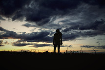 silhouette standing under a cloudy sky at dusk