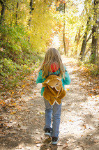 Girl walking through a forest with backpack