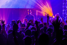 Worship service hands raised crowd of worshipers worship leader singing purple church