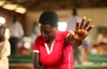 Woman in worship service with raised hands