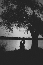 A couple embraces one another at the edge of a pond