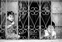 Children playing behind wire fencing