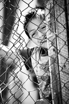 Child playing behind chain fence