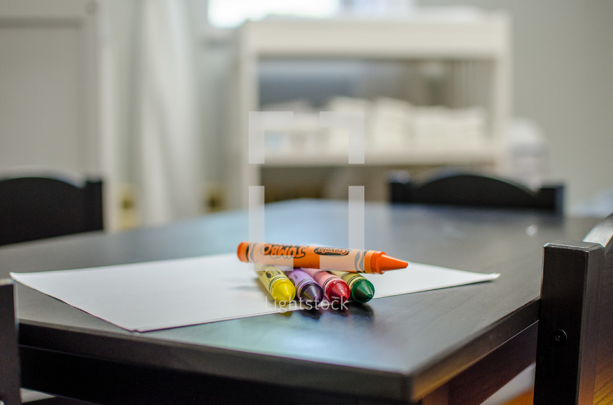 crayons on white paper on a table