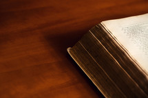 edge of a Bible on a wood table