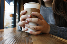 a young woman holding a coffee cup
